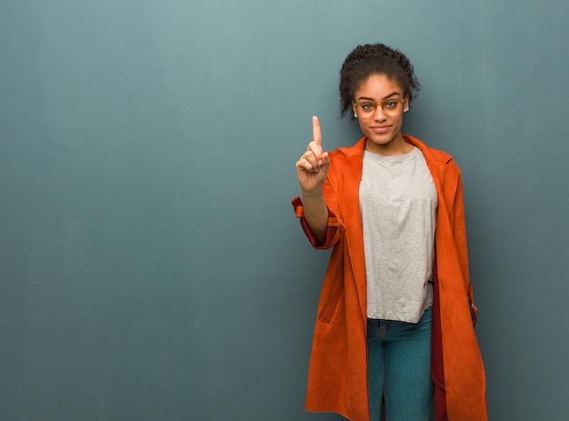 Jovem garota afro-americana negra com olhos azuis, mostrando o número um