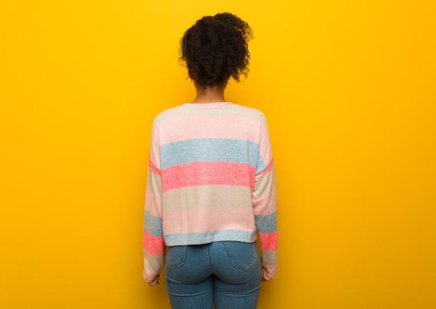 Jovem garota afro-americana negra com olhos azuis por trás, olhando para trás