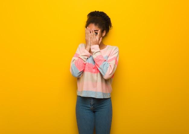 Jovem garota afro-americana negra com olhos azuis se sente preocupada e assustada