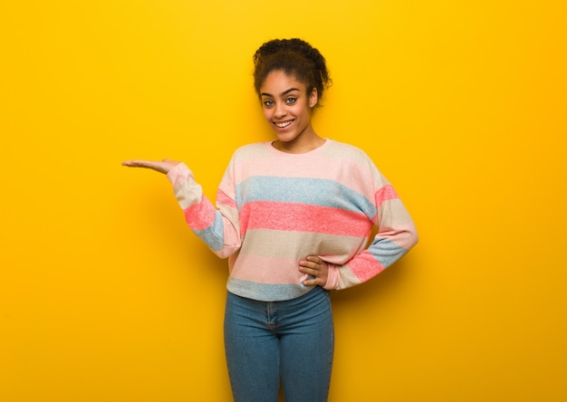 Jovem garota afro-americana negra com olhos azuis, segurando algo com a mão