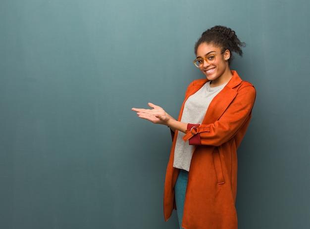 Jovem garota afro-americana negra com olhos azuis, segurando algo com as mãos