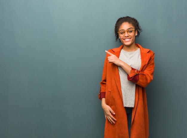 Jovem garota afro-americana negra com olhos azuis, sorrindo e apontando para o lado