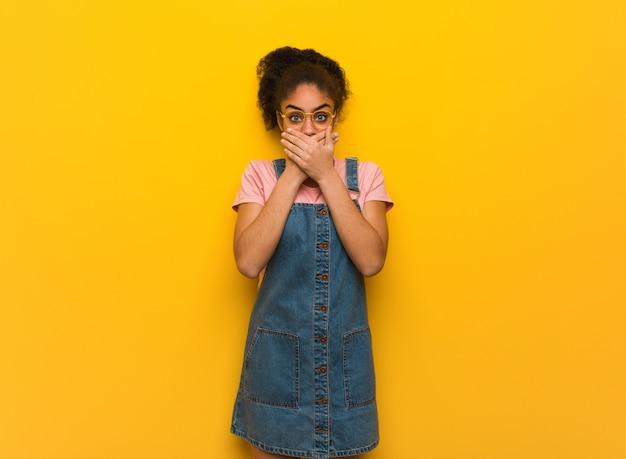 Jovem garota afro-americana negra com olhos azuis, surpresa e chocada