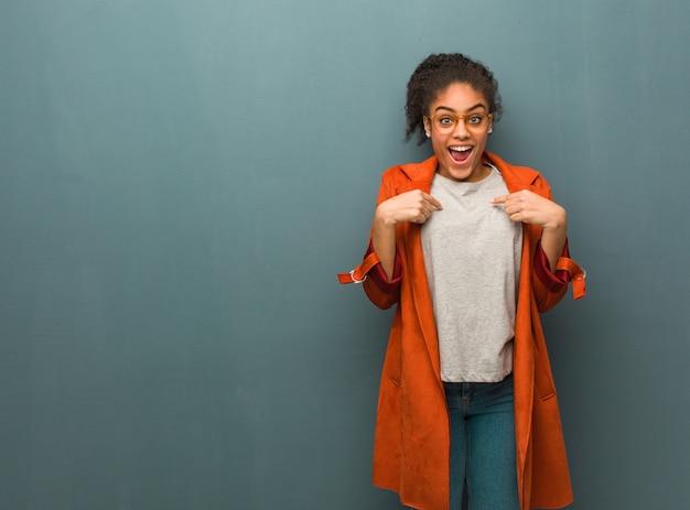 Jovem garota afro-americana negra com olhos azuis surpresa, sente-se bem-sucedida e próspera