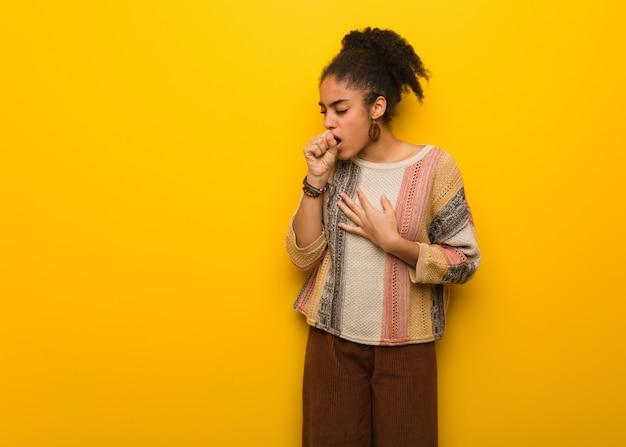 Jovem garota afro-americana negra com olhos azuis, tossindo, doente devido a um vírus ou infecção