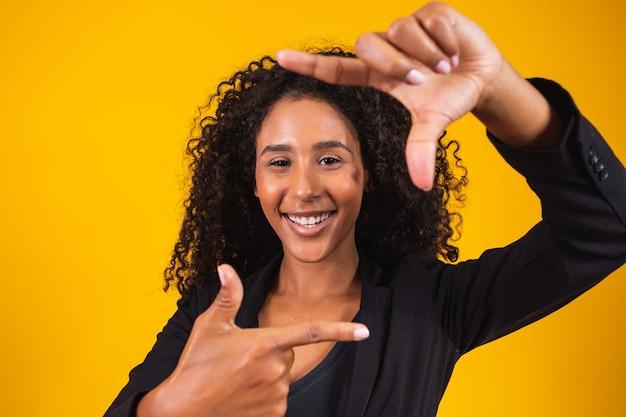 Jovem garota afro-americana, vestindo roupas executivas, sorrindo fazendo moldura com as mãos e os dedos com uma cara feliz. criatividade e conceito de fotografia.