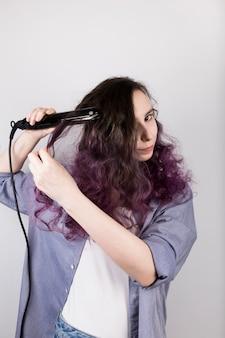 Jovem garota alisa o cabelo encaracolado de chapinha