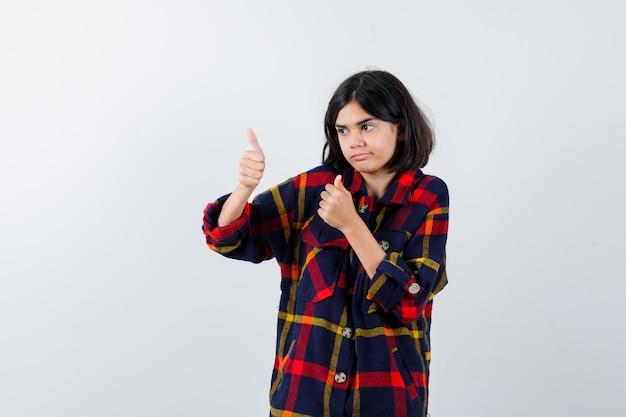 Jovem garota aparecendo dois polegares para cima em uma camisa e olhando feliz, vista frontal.