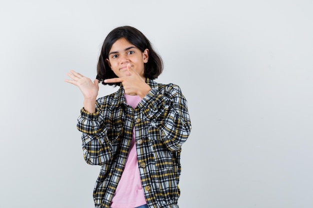 Jovem garota apontando a mão com o dedo indicador em uma camisa e camiseta rosa e está linda. vista frontal.