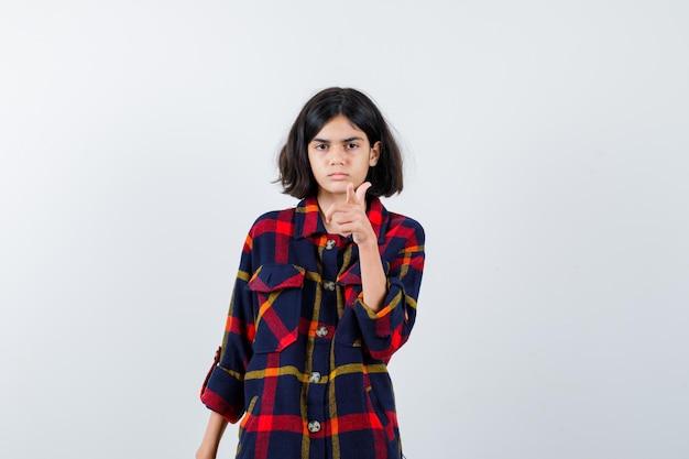 Jovem garota apontando com o dedo indicador em uma camisa e olhando séria. vista frontal.
