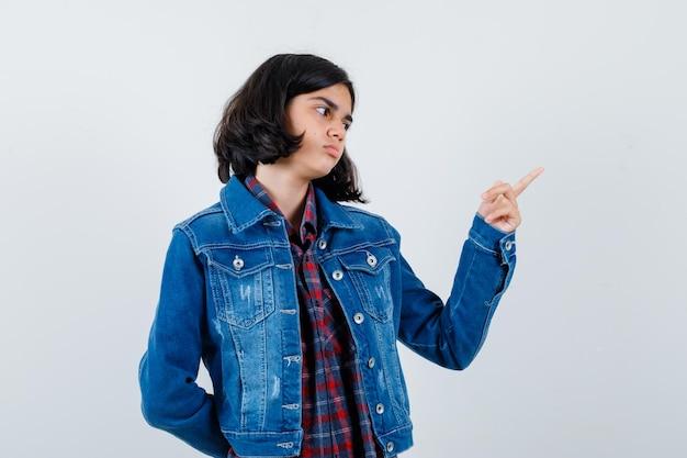 Jovem garota apontando para a direita com o dedo indicador em camisa e jaqueta jeans e parecendo calma. vista frontal.
