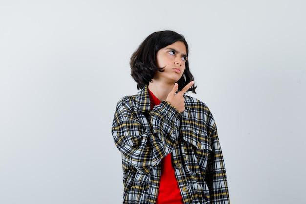Jovem garota apontando para a direita com o dedo indicador em camisa xadrez e camiseta vermelha e olhando séria. vista frontal.