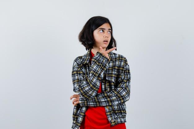Jovem garota apontando para a direita com o dedo indicador em uma camisa e camiseta vermelha e olhando surpresa, vista frontal.