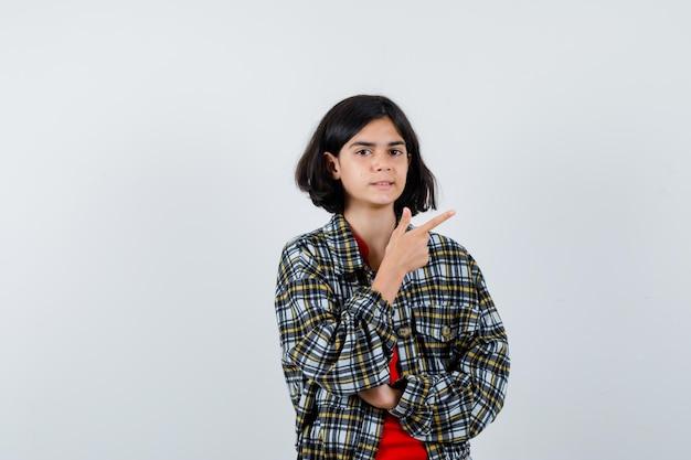 Jovem garota apontando para a direita com o dedo indicador em uma camisa xadrez e uma camiseta vermelha e olhando bonita, vista frontal.