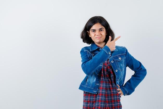 Jovem garota apontando para a direita com o dedo indicador, segurando a mão na cintura em uma camisa quadriculada e jaqueta jeans e olhando bonita, vista frontal.