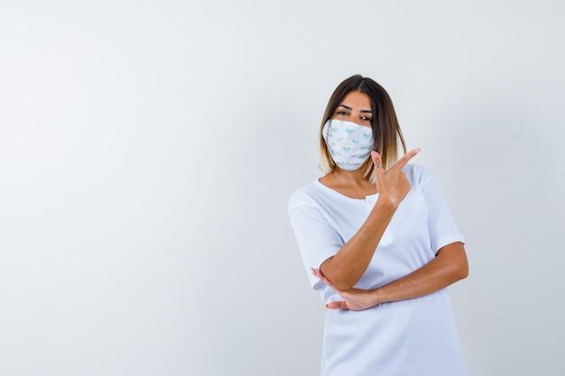 Jovem garota apontando para a direita com o dedo indicador, segurando a mão sob o cotovelo em uma camiseta branca e uma máscara e olhando confiante, vista frontal.