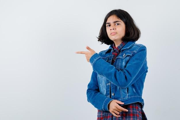Jovem garota apontando para a esquerda com o dedo indicador em camisa e jaqueta jeans e olhando sério, vista frontal.