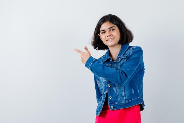 Jovem garota apontando para a esquerda com o dedo indicador em t-shirt vermelha e jaqueta jeans e olhando feliz, vista frontal.