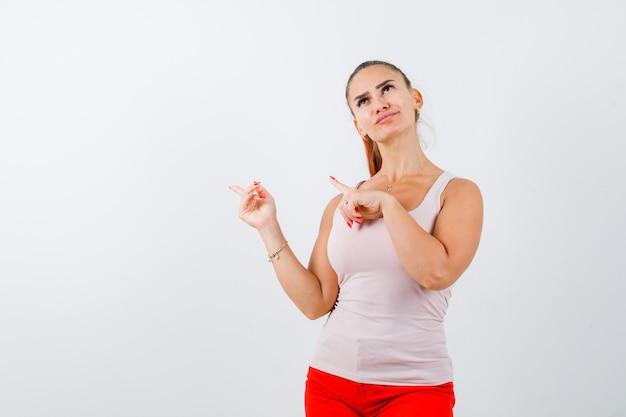 Jovem garota apontando para a esquerda com o dedo indicador em uma calça bege e vermelha e olhando pensativa, vista frontal.