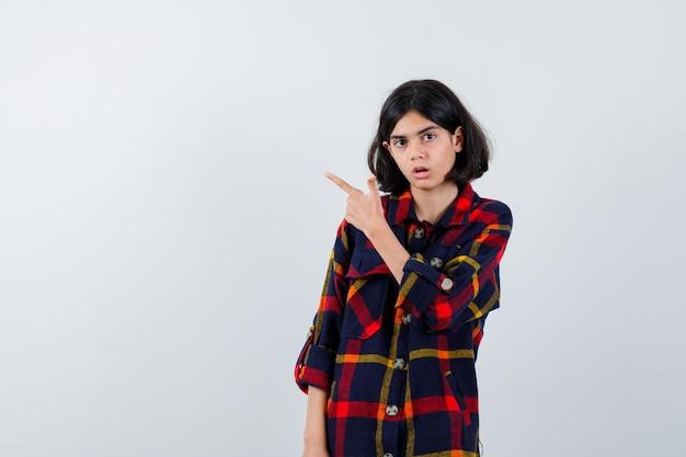Jovem garota apontando para a esquerda com o dedo indicador em uma camisa e parecendo surpresa. vista frontal.