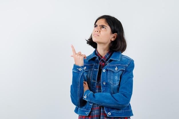 Jovem garota apontando para cima com o dedo indicador em camisa e jaqueta jeans e olhando pensativa, vista frontal.