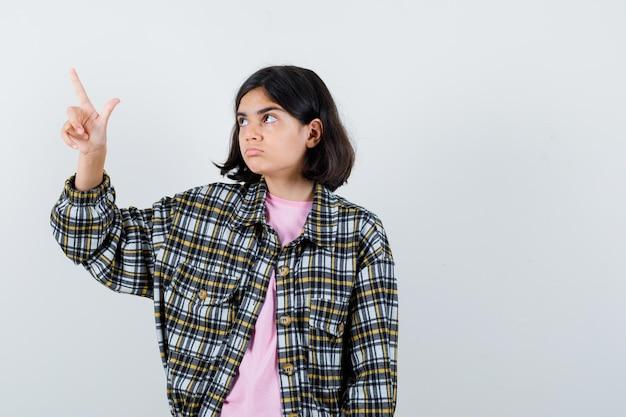 Jovem garota apontando para cima com o dedo indicador, olhando para longe em uma camisa xadrez e camiseta rosa e olhando pensativa, vista frontal.