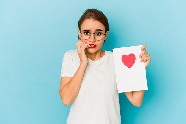 Jovem garota árabe magra segurando um cartão de dia dos namorados, roendo as unhas, nervosa e muito ansiosa.