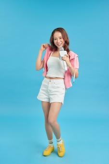 Jovem garota asiática feliz e animada cantando uma música de karaokê online com microfone e pulando