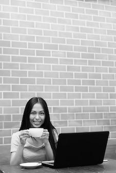 Jovem garota asiática feliz sorrindo enquanto bebia cappuccino com o laptop na mesa de madeira na parede de tijolos