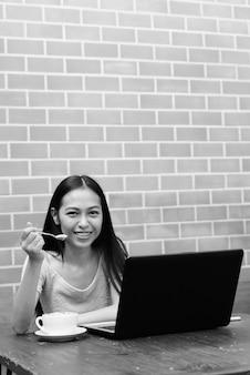 Jovem garota asiática feliz sorrindo enquanto come a espuma do cappuccino com o laptop na mesa de madeira na parede de tijolos