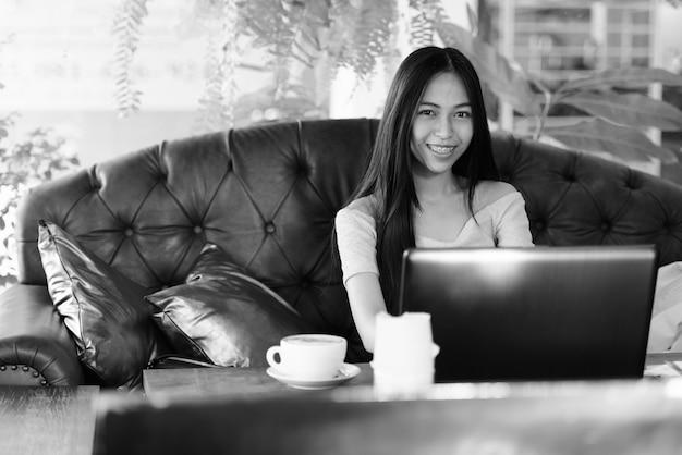 Jovem garota asiática feliz sorrindo enquanto está sentada em um café ao ar livre com um laptop e um cappuccino na mesa de madeira