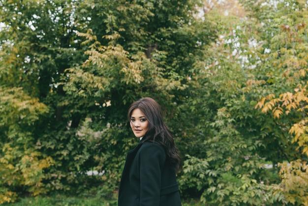 Jovem garota asiática sorridente na frente das árvores de outono. foco seletivo