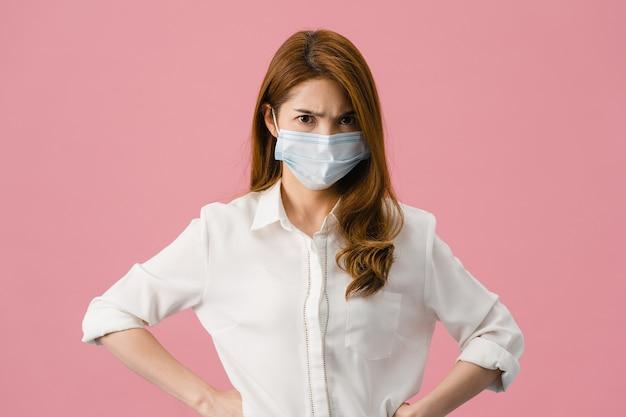 Jovem garota asiática usar máscara médica com expressão negativa, grito animado, choro de raiva emocional e olhar para a câmera isolada no fundo rosa. s