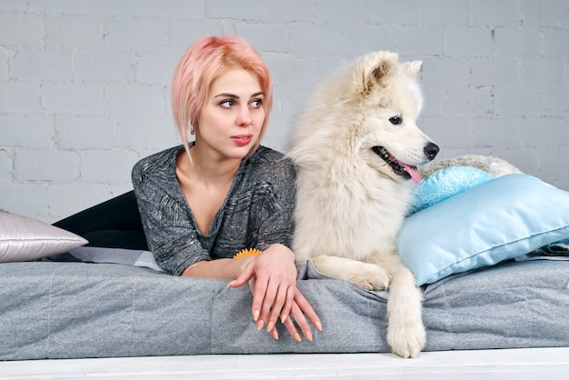 Jovem garota atraente com um corte de cabelo curto e cabelo loiro, juntamente com seu grande cachorro branco samoiedo deitado na cama e olhando por cima.