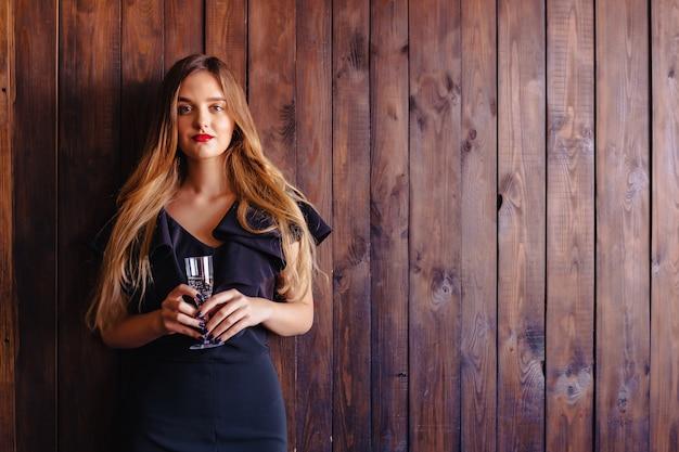 Jovem garota atraente com uma taça de champanhe ou vinho no fundo da parede