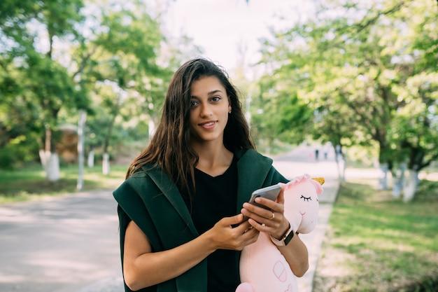 Jovem garota atraente digitando mensagens em seu celular.