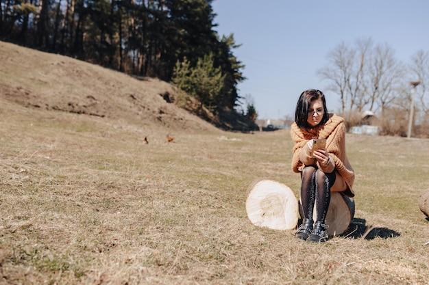 Jovem garota atraente e elegante na natureza em fundo de floresta com telefone em um dia ensolarado
