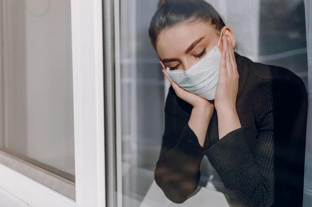 Jovem garota atraente em uma máscara médica protetora olha pela janela. isolamento durante a epidemia. isolamento em casa.