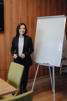 Jovem garota atraente emocional em roupas de estilo comercial, trabalhando com flipchart em um escritório ou audiência moderna