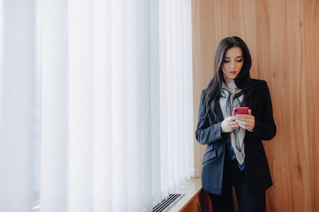 Jovem garota atraente emocional em roupas de estilo empresarial em uma janela com um telefone em um escritório ou auditório moderno