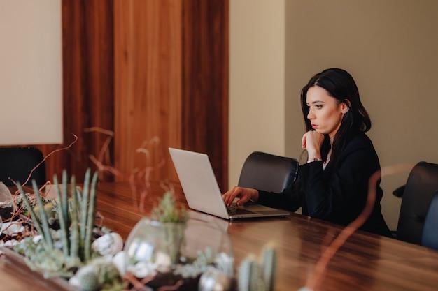 Jovem garota atraente emocional em roupas de estilo empresarial, sentado em uma mesa em um laptop e telefone no escritório ou auditório