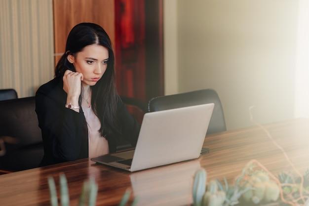 Jovem garota atraente emocional em roupas de negócios, sentado em uma mesa em um laptop e telefone
