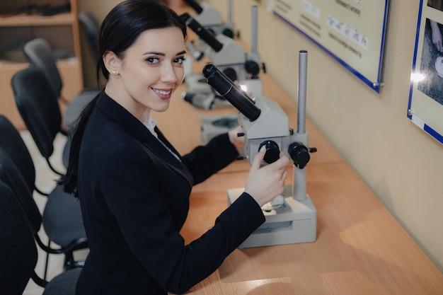 Jovem garota atraente emocional, sentado à mesa e trabalhando com um microscópio em um escritório ou audiência moderna