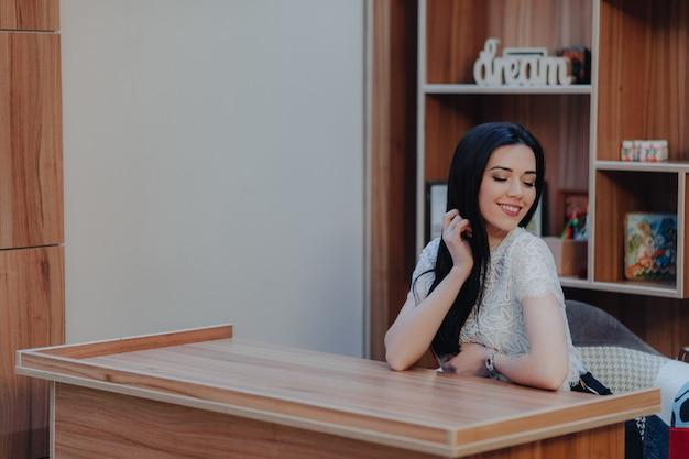 Jovem garota atraente emocional sentado em uma mesa