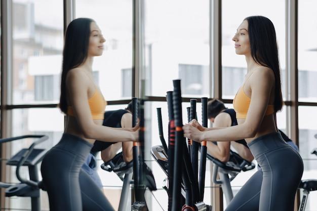 Jovem garota atraente no ginásio na bicicleta ergométrica, fitness e yoga