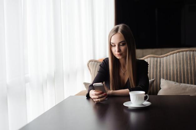 Jovem garota atraente sentada sozinha perto de uma janela grande