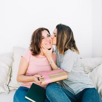 Jovem garota beijando mulher na bochecha em casa