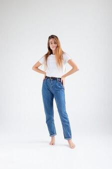 Jovem garota bonita caucasiana com cabelo comprido em uma camiseta jeans azul no estúdio