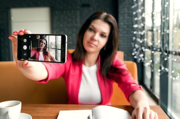 Jovem garota bonita fazendo selfie sentado no café.