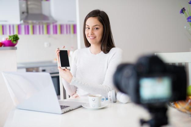 Jovem garota bonita feliz está sentado na mesa da cozinha e mostrando o telefone para a câmera com o laptop na frente dela enquanto bebe café.